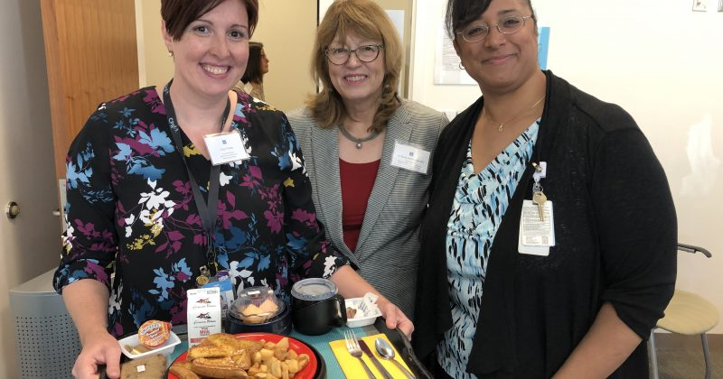 """Dr. Busby-Whitehead with Nutrition and Food Services Dementia Champion Tracy Thorp and Clinical Nurse Education Specialist Krista Wells, featuring the """"dementia-friendly food tray.'"""