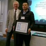 Postdoc from Aziz Sancar lab Wentao Li holds plaque from UNC PARE award 2018 ceremony