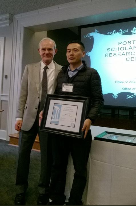 Postdoc from Aziz Sancar lab Wentao Li holds plaque from UNC PARE award 2018 ceremony