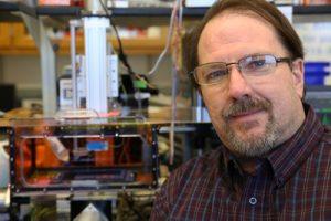 photo of Brian Button PhD, Associate Professor of Biochemistry and Biophysics near equipment
