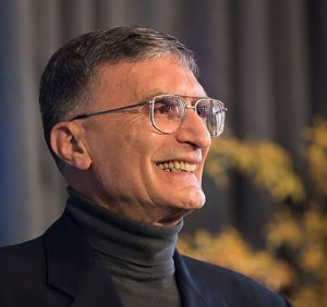 photo of face of Aziz Sancar at nobel event at David library April 2016 with yellow flowers in background