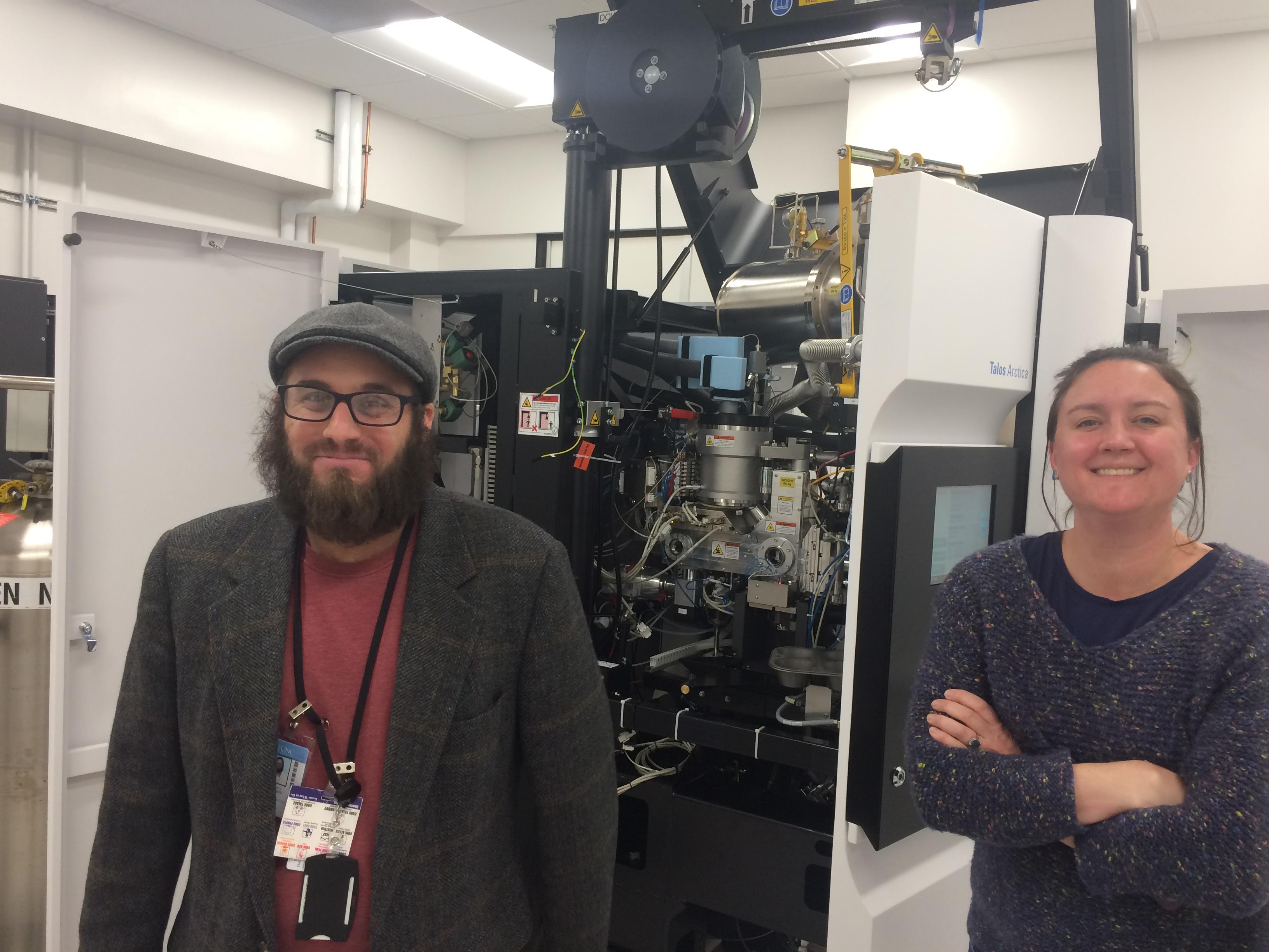 Joshua Strauss and Saskia Neher stand beside the Cryo-EM equipment