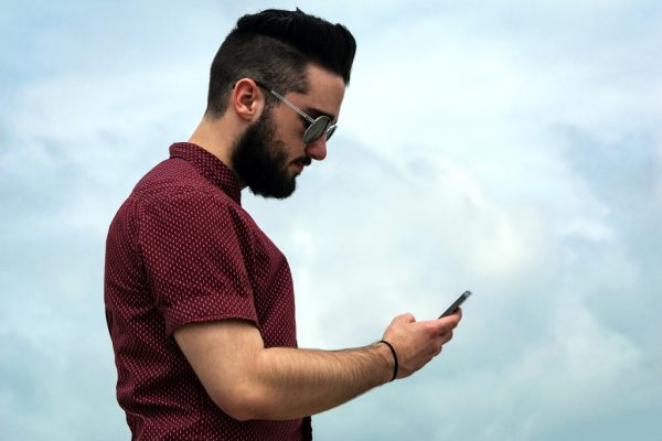 man with a beard and a red shirt holding a cell phone