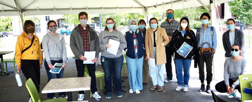 earth day 2021 people outside holding finished surveys
