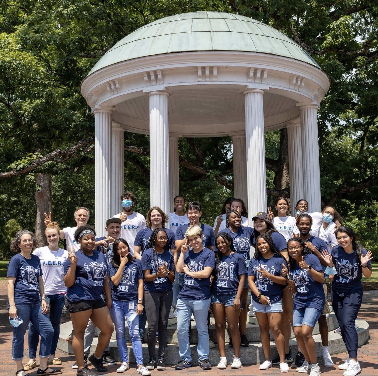 24 diverse students and 2 faculty standing by old well for UNC SURE 2021 program