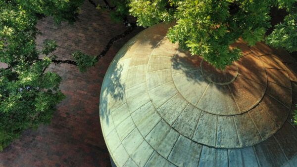 top of old well from sky with green trees
