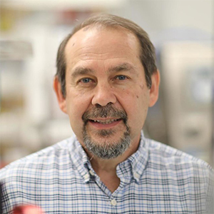 Closeup of Dr. Jude Samulski in front of a window in his office on UNC campus. Link goes to highlights of this story in Gene Therapy Center website news: https://www.med.unc.edu/genetherapy/a-boy-with-muscular-dystrophy-was-headed-for-a-wheelchair-then-gene-therapy-arrived/