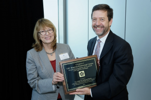 Dr. Jan Busby-Whitehead presents UNC Hospitals Hillsborough Campus Vice President Jeff Strickler with a plaque in recognition of Hillsborough's hospital-wide dementia friendly training.