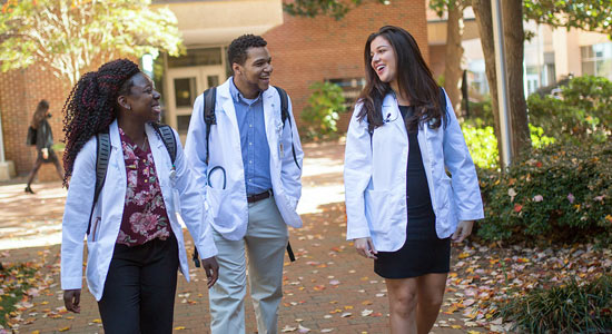 three medical students in white coats walking on campus together.