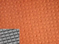 an orange grid of raised squares with the lower left hand corner in gray showing the 3D quality in more detail