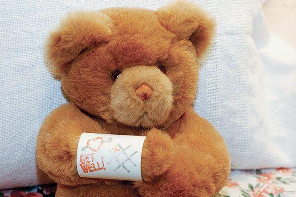 hurt teddy bear with bandaged arm.