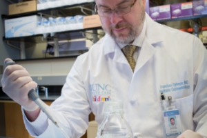 Dr. Sylvester using a pipette in his lab