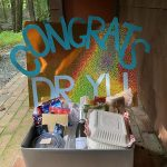 """A box of celebration goodies on a break entrance with a colorful poster behind it with the words, """"Congrats Waylin Yu!"""" on it."""
