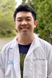 Waylin Yu, PhD, in his PHCO Alumni Coat in honor of earning his PhD, which is a white lab coat that has UNC Pharmacology and his name, Dr. Waylin Yu embroidered on it in UNC blue.