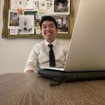 Waylin Yu smiles while seated with his laptop for his PhD defense.
