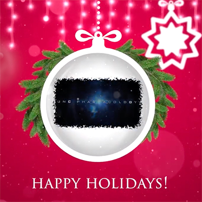 """The words """"Happy Holidays!"""" on a red background and a white ornament topped with greenery and the words """"UNC Pharmacoloogy"""" on it."""