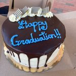 """Graduation 2021 celebration cake chocolate icing and carolina blue words """"Happy Graduation"""" on it with white frosting flowers and brown and white striped chocolate squares as decoration"""