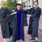 Dr. Amy Pomeroy, hooding ceremony, 2021 graduation with mentors, Dr. Henrik Dohlman and Dr. Tim Elston adjusting her PhD hood