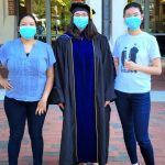 3 women with masks on stand together. Dr. Amy Pomeroy, in the center, is dressed in her PhD gown.