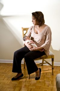 Mother with sad expression holding newborn