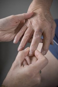 A doctor inspects a patient's hand.